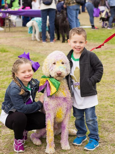 A colorful pooch and kids enjoy the Krewe of PAWS annual