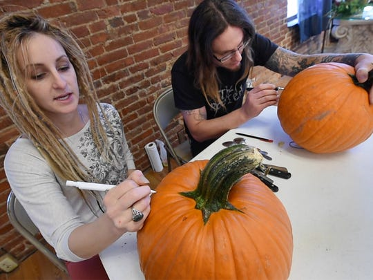 Jessica Flynn, left, and Dustin Nispel, co-owners of The Rooted Artist Collective in York, carve pumpkins at the gallery.