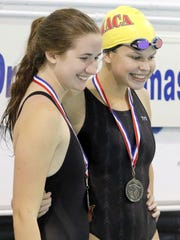 Paige Kieper of Lansing (left) and Annika Browning of Ithaca are shown with their medals after tying for first in the 100-yard backstroke at the Jack Thomas Invitational on Saturday in Elmira.
