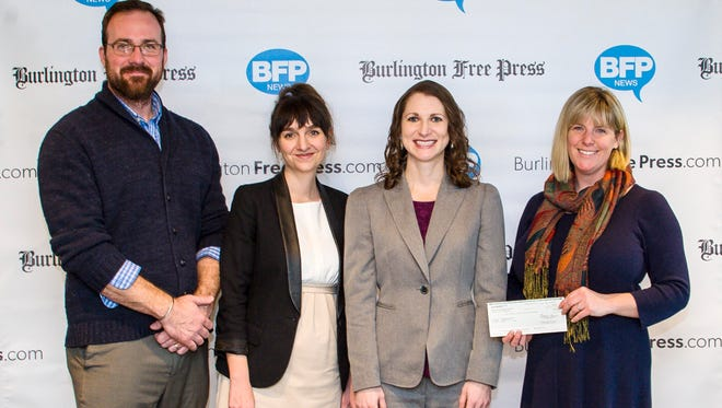 Cassie Lindsay, Donor and Corporate Relations Manager for the Vermont Foodbank, right, accepts a check from, from left, Pat McDonough, Free Press Media Distribution Manager; Kasia Abrams, Free Press Media Consumer Sales and Marketing Manager; and Samara Bushey, Director of Operations for the local Hannaford  supermarkets, in Burlington on Thursday, March 9, 2017.