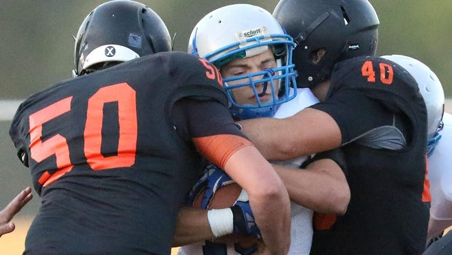 Blanchets Jared Myers is tackled by Scio's Dillion Wallen (50) and Logan Gray (40) during their game on Friday, Sept. 18, 2015, in Scio, Ore.