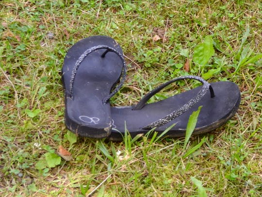 A pair of wet flip flops lay abandoned by the water's
