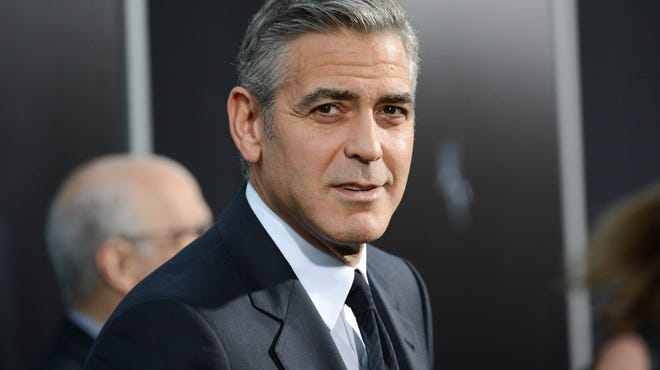 """In this Oct. 1, 2013 file photo actor George Clooney attends the premiere of """"Gravity"""" at the AMC Lincoln Square Theaters, in New York. George Clooney has chastised a British newspaper over an article claiming his fiancee's mother disapproves of the impending marriage for religious reasons. Clooney said that the claims about his future mother-in-law Baria Alamuddin were untrue and irresponsible."""