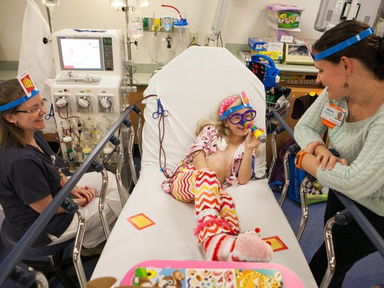 Avery Watts, 7, is plugged into a machine that filters her blood, removing the high levels of cholesterol as she plays a game of Hedbanz with register nurse Starr Messer (left) and child life specialist Melissa Nicely (right) at Nemours/A.I. duPont Hospital for Children.