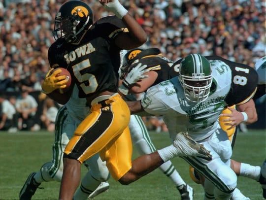 Iowa's Sedrick Shaw (5) runs past a tackle by MSU's