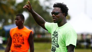 Former NFL player and Immokalee native Edgerrin James coaches participants in a game of 7-on-7 during his annual free youth football camp at North Park in Ave Maria on Monday, July 20, 2015. (Scott McIntyre/Naples Daily News)
