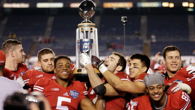 Wisconsin players hold the Holiday Bowl trophy after defeating Southern California in the Holiday Bowl NCAA college football game on Wednesday in San Diego. Wisconsin won 23-21.