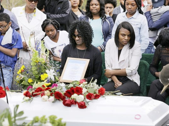 Gloria Darden, mother of Freddie Gray, center, sits in front of Gray's casket at his burial, Monday, April 27, 2015, at Woodlawn Cemetery in Baltimore. Gray died from spinal injuries about a week after he was arrested and transported in a Baltimore Police Department van.