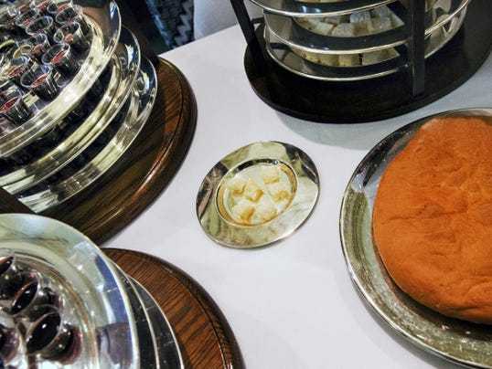The gluten-free host is on the tiny silver plate surrounded by traditional bread and wine at First Presbyterian Church of York. The congregation freezes the bread that is sliced, so that a tiny amount can be prepared for each service.