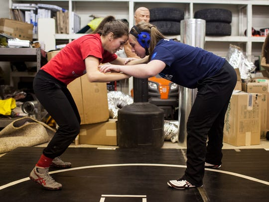 Morgan Huff, 17, wrestles Courtney Lillich, 15, on