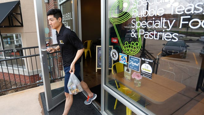HungryBoiler driver Eric Koo picks up bubble tea from Latea Bubble Tea Lounge, 358 E. State Street, for a delivery Monday, March 28, 2016, in West Lafayette. Koo will delivered the bubble tea to a Purdue University student in First Street Towers. Koo said he averages about 30 deliveries a day for HungryBoiler.