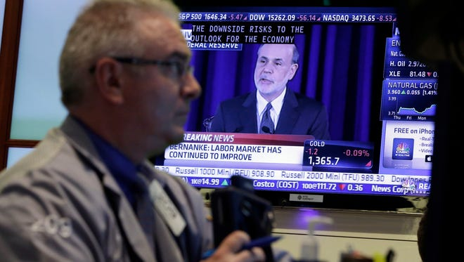 Fed Chairman Ben Bernanke on a TV screen at the New York Stock exchange in June.