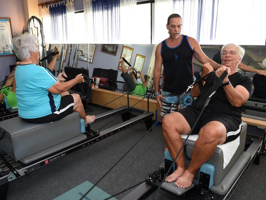 Director Pepe Laflamme helps Lana Leffingwell, 73, right, with her form at Nuform, Innovative Fitness in Tamuning on March 15.  Leffingwell plays golf two to three times a week with her friend Susan, 79, wearing blue.