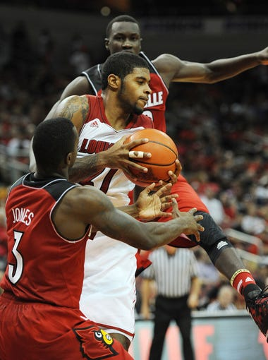 Chane Behanan (center) pulls down a rebound over Chris Jones (left) and Mangok Mathiang (right) during the Red-White Scrimmage game at the KFC Yum! Center on Saturday. Oct. 12, 2013