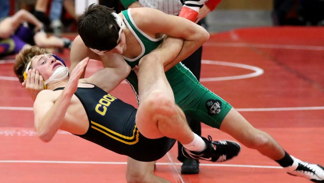 Port Washington's Oliver Rosado drives Oconomowoc's Coby Ganser to the mat in a 126-pound match during the Highlander Varsity Invitational at Homestead High School on Jan. 19.
