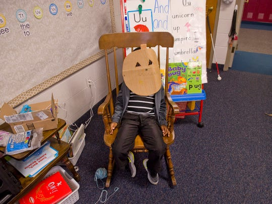 JaCory Copeland takes a break in the class rocking chair after crafting his cardboard costume, a pumpkin head mask, in Lauren Hartmayer's kindergarten class at Delaware Elementary School Monday afternoon.