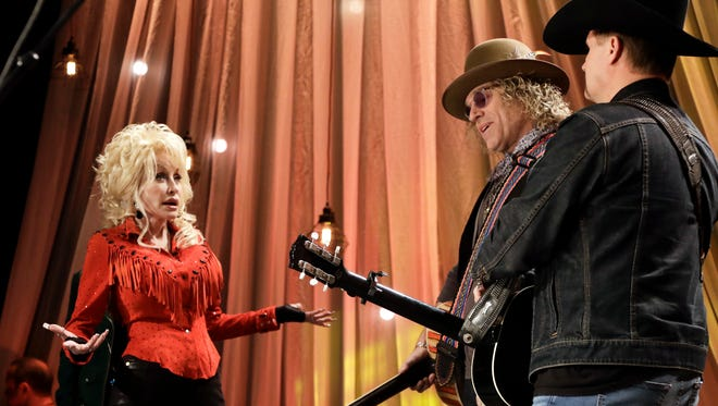 Dolly Parton talks with Kenny Alphin, center, and John Rich, right, of the country music duo Big & Rich, during tapings for Dolly Parton's Smoky Mountain Rise Telethon Tuesday, Dec. 13, 2016, in Nashville, Tenn.