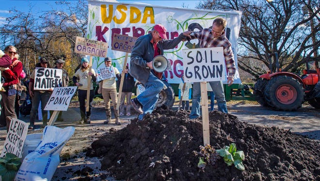 Pete Johnson of Craftsbury, right, helps fellow organic farmer Jake Guest of Norwich climb a pile of organic manure as they both rally against proposed regulations that would permit crops grown with hydroponics to be considered organic in Stowe on Monday, October 26, 2015.