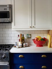 The kitchen in a renovated apartment has marble counters.