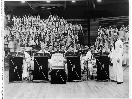 Members of the USS Arizona dance band pause at Bloch Arena, Pearl Harbor, during the Battle of Music semifinal held Nov. 22, 1941. From left, they are Musician 2nd Class Curtis Haas, Musician 2nd Class Gerald Cox, Musician 2nd Class Ernest Whitson Jr., Musician 2nd Class Frank Floege, Musician 2nd Class Clyde Williams, Musician 2nd Class Bernard Hughes, Musician 2nd Class Alexander Nadel, Musician 2nd Class Charles White, Musician 2nd Class Robert Shaw, Musician 2nd Class Harry Chermucha, Musician 2nd Class William Moorhouse, Musician 2nd Class Emmett Lynch, Musician 2nd Class Wayne Bandy, Musician 2nd Class Jack Scruggs, Musician 2nd Class James Sanderson, and Musician 1st Class Frederick Kinney. (Photo: Official U.S. Navy photo)