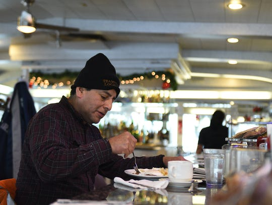 Juan Aparicio, 55, from North Arlington, braves the storm for a bite at the Arlington Diner on Thursday.