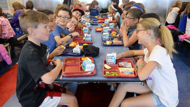 Students socialize during lunch at Bethke Elementary School in Timnath on Monday, April 4, 2016.