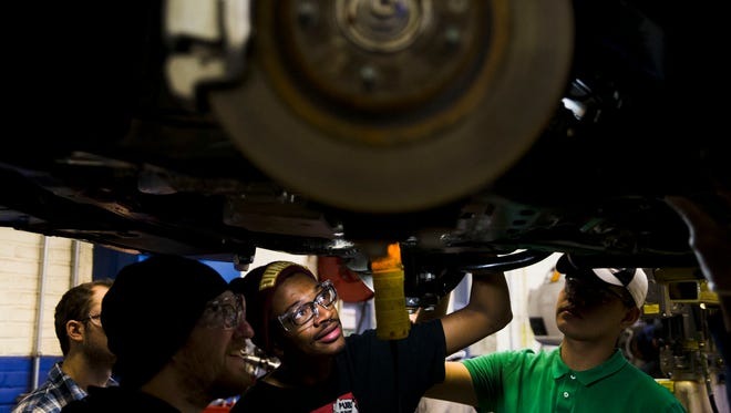 Automotive service technology students work on a car at the Community College of Philadelphia, in Philadelphia, in late October 2014. The U.S. Labor Department reports on the number of people who applied for unemployment benefits for the week ending Nov. 15 on Nov. 20.