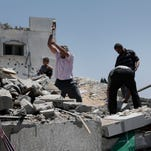 Palestinians search the rubble of a house destroyed in an Israeli airstrike in Gaza City.