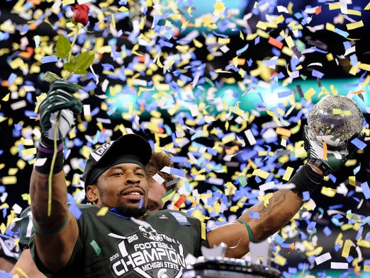 Michigan State's Denicos Allen holds the Amos Alonzo Stagg Championship Trophy after their 34-24 victory over Ohio State in the Big Ten Championship game, Saturday, December 7, 2013, at Lucas Oil Stadium.