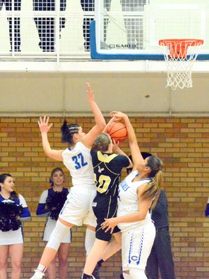 Carlsbad's Kim Best (32) and Kaliah Montoya (54) make contact with Hobbs' Payton O'Brain in the first quarter Tuesday.