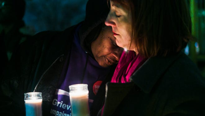 """December 14, 2016 - Joyce Johnson rests her head on Lorrie Garcia's shoulder during a candlelight vigil called, """"Light the Night for Peace,"""" at Morris Park on Wednesday. St. Mary's Episcopal Cathedral and Moms Demand Action for Gun Sense held the vigil on the anniversary of the shootings at Sandy Hook Elementary School and to remember every life lost to gun violence this year in Memphis. Johnson's 22-year-old son, Tremaine Artry, was shot and killed on January 13, 2014."""