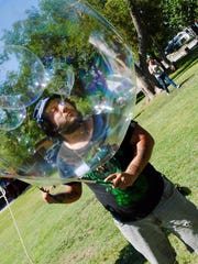 Blowing bubbles within bubbles, Love Vazquez entertains kids attending the Pride Week kickoff Saturday, June 17, 2017 at Womens Pioneer Park.
