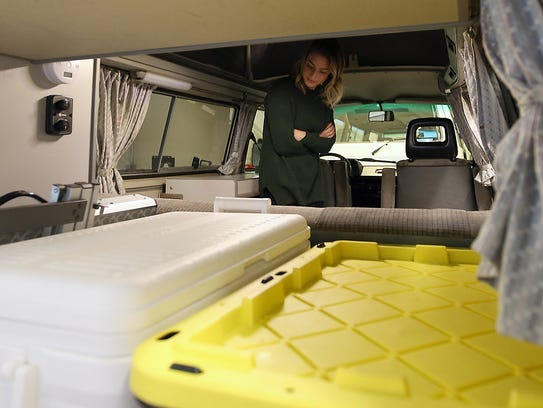PacWesty's Nora Phillips is framed by the back cargo area of the camper van while talking about the various amenities located inside.