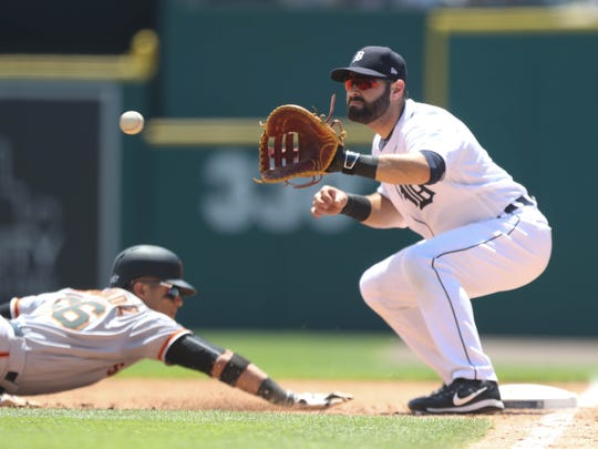 Alex Avila holds the Giants' Gorkys Hernandez at first