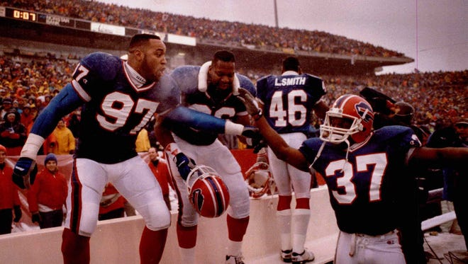 Buffalo Bills, from left, Cornelius Bennett (97), Leon Seals (96) and Nate Odomes (37) celebrate a victory over the Miami Dolphins in 1991.