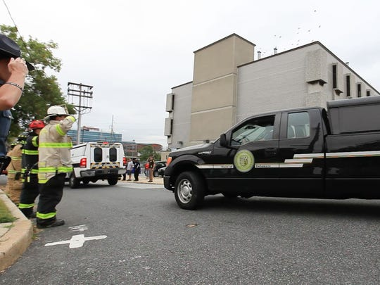 A motorcade arrives at the Delaware medical examiner's office carrying the bodies of two firefighters killed in a blaze early Saturday morning. A floor of a Canby Park rowhouse collapsed.