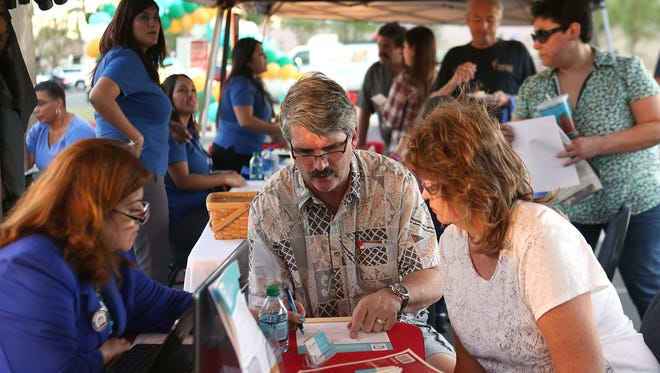 Brandon and Dawn LeValley, right,  receive information about the Covered California health insurance exchange during a promotional stop at JFK Memorial Hospital in Indio on Nov. 2, 2015.