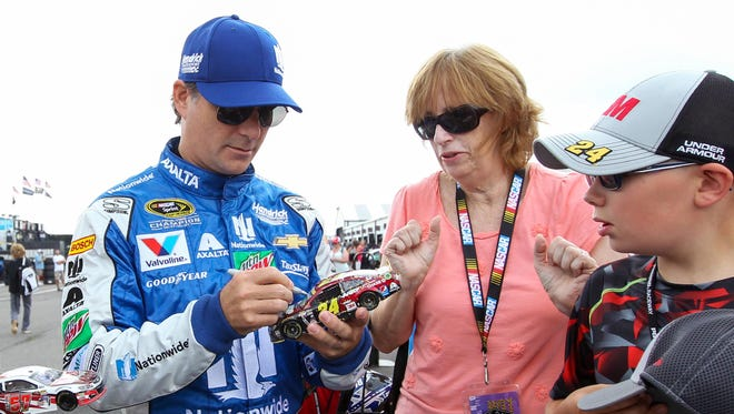 Jeff Gordon signs autographs during practice for the Pennsylvania 400 at Pocono Raceway on Friday.