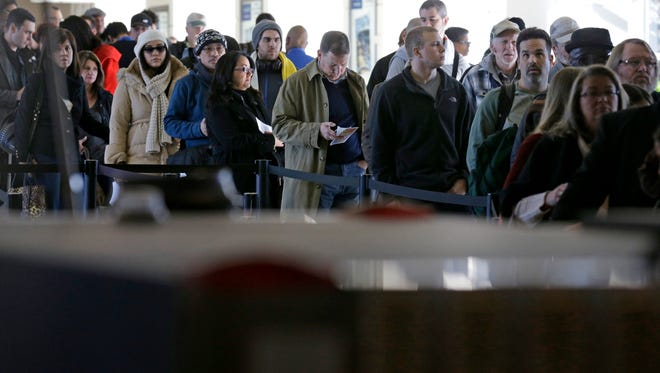 Travelers wait in line to check in at a security checkpoints area at Chicago's Midway Airport on Nov. 21, 2014.