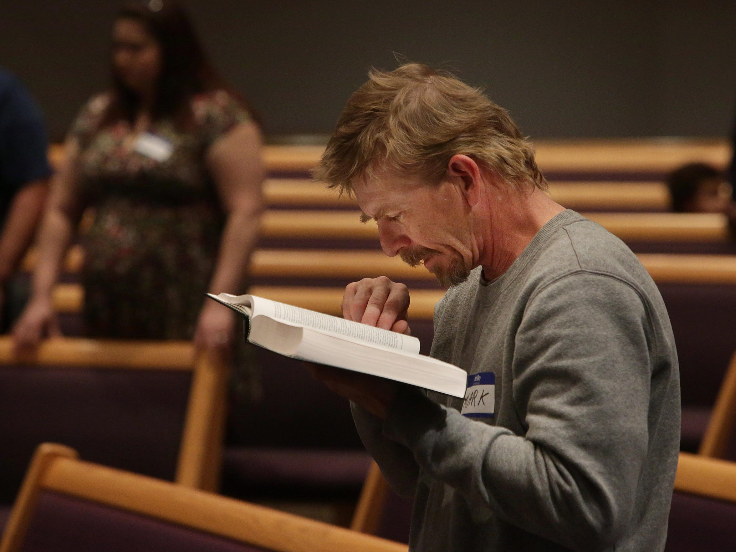 Newly formed CityReach Church is led by Pastor John Alarid and his wife, Hannah. Mark Smith reads the bible during the sermon.