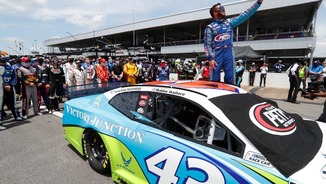Driver Bubba Wallace takes a selfie with himself and other drivers after they pushed his car to the front in the pits of the Talladega Superspeedway prior to the start of the NASCAR Cup Series race on Monday.
