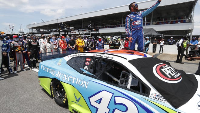 Driver Bubba Wallace takes a selfie with himself and other drivers who pushed his car to the front in the pits at Talladega Superspeedway prior to the start of Monday's  NASCAR Cup Series auto race. In an extraordinary act of solidarity with NASCAR's only Black driver, dozens of drivers pushed Wallace's car to the front of the field before Monday's race as FBI agents nearby tried to find out who left a noose in his garage stall over the weekend.