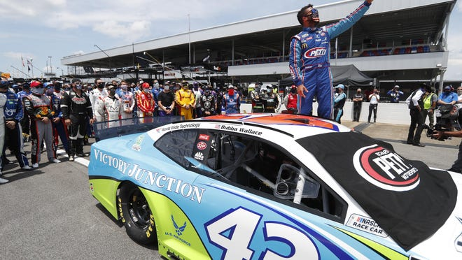 Bubba Wallace takes a selfie of himself and of other drivers who had pushed his car to the front in the pits at Talladega Superspeedway before the NASCAR Cup Series auto race in Talladega Ala., Monday June 22, 2020.