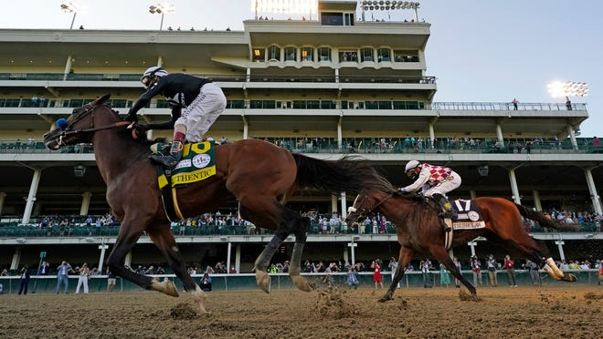 Jockey John Velazquez riding Authentic, right, crosses the finish line ahead of jockey Manny Franco riding Tiz the Law to win Saturday's Kentucky Derby at Churchill Downs.
