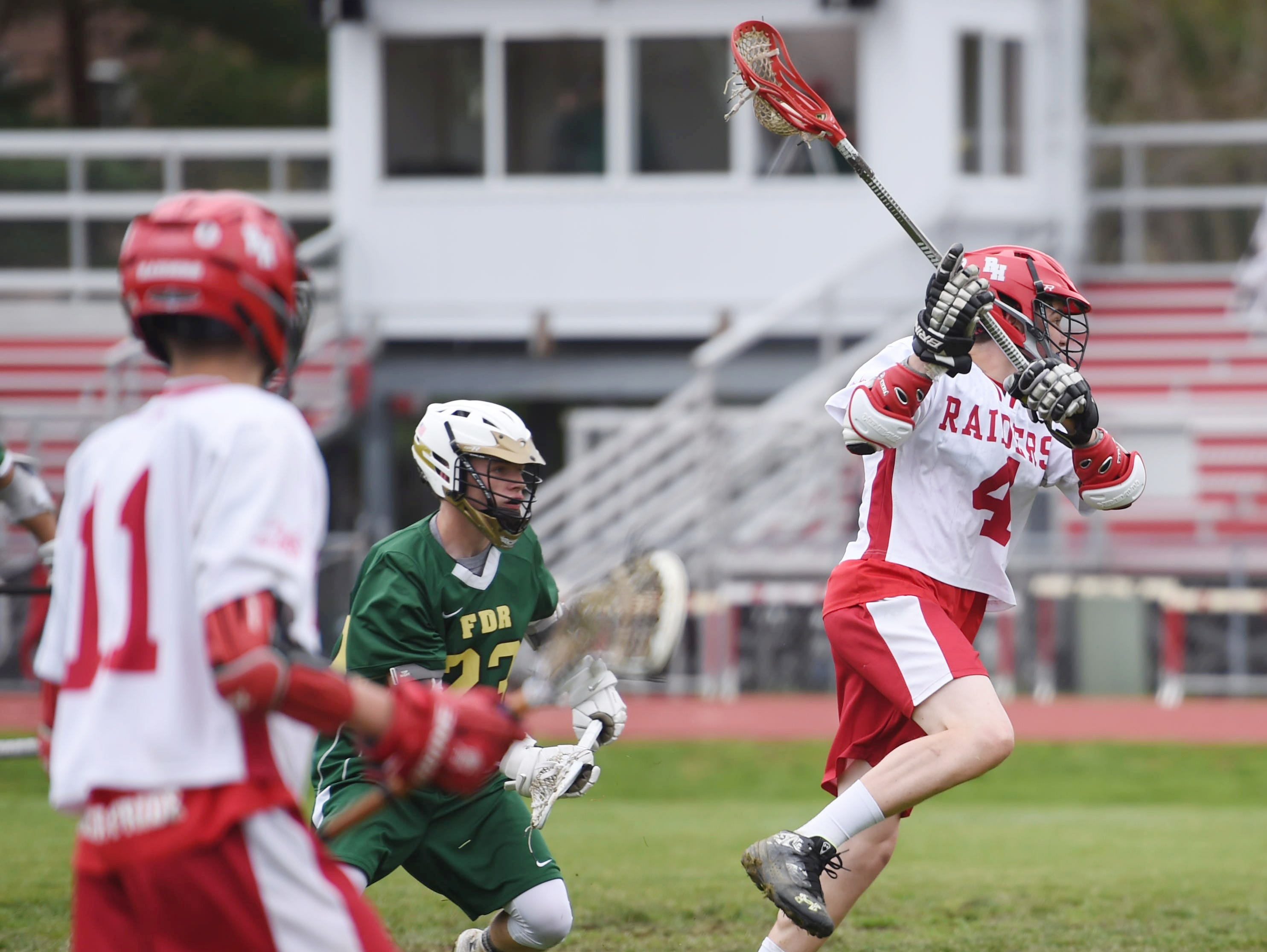 Red Hook's Cam Hackett leaps ahead of FDR's Travis Slocum to take a shot on goal during Tuesday's home game.