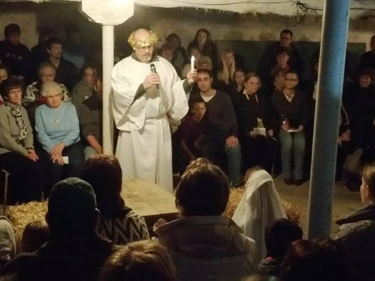 An angel, played by Peter Schuerman, stands over Mary and Joseph during the Live Christmas Nativity.