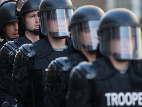 Riot police stand in formation as a protest forms in