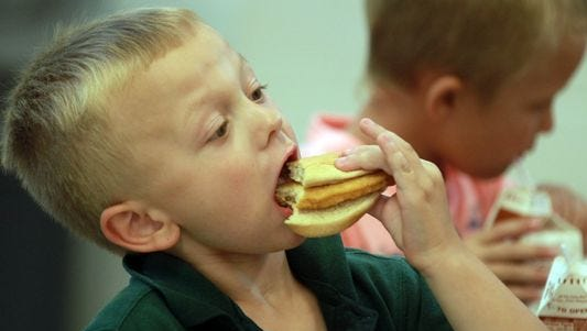 Silver Grove Schools second-grader Eddie Buttery chomps into a chicken sandwich during lunch.