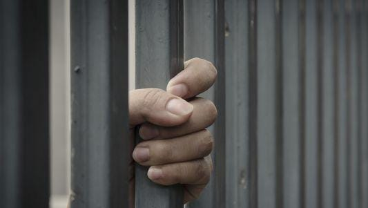 A file photo of a prisoner holding on to the jail cell bars.