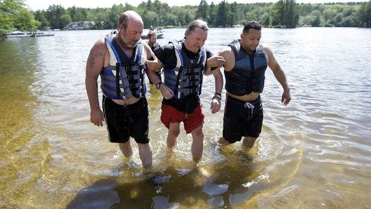 Army Vietnam combat veteran William Long, 65, of New Haven, Conn., center, is escorted from the water by volunteers after water skiing during an adapted sports program for veterans, in Coventry, R.I. Long, who lives with Parkinson's disease, was exposed to the herbicide Agent Orange while serving in Vietnam.